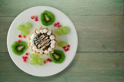 Dessert of cake and fruit grapes, kiwi, pomegranate on a woode Stock Photography