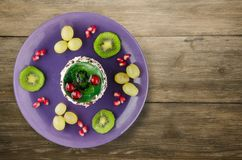 Dessert of cake and fruit grapes, kiwi, pomegranate on a woode Stock Image