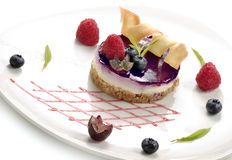 Dessert, cheesecake with berries. On white plate Stock Photos