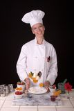 Dessert Chef. Assertive posed uniformed female Pastry Chef standing at her dessert station behind her apricot preserve with vanilla ice cream creation Stock Image
