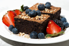 Dessert - chocolate brownies with fresh berries on plate Royalty Free Stock Images