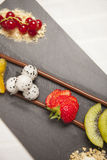 Dessert of chocolate and fruit. Dessert of chocolate sticks and pieces of fruit on a black plate Stock Image