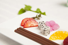 Dessert of chocolate and fruit. Dessert of chocolate sticks and pieces of fruit on a white plate Stock Images