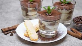 Dessert classico di tiramisù in tazza di vetro e biscotti di savoiardi sul piatto su fondo concreto video d archivio