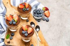 Dessert classique de tiramisu avec des myrtilles et des fraises dans un verre sur le fond concret image stock