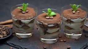 Dessert classique de tiramisu dans un verre sur le conseil servant en pierre sur le fond concret foncé clips vidéos