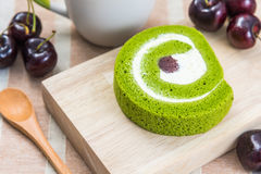 Dessert and Coffee. Green tea roll cake on wood plate with a cup of coffee and cherries Royalty Free Stock Images
