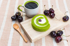 Dessert and Coffee. Green tea roll cake on wood plate with a cup of coffee and cherries Stock Photo