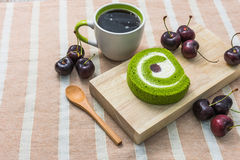 Dessert and Coffee. Green tea roll cake on wood plate with a cup of coffee and cherries Royalty Free Stock Photography