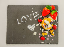 Dessert con frutta su un piatto di pietra nero con un lo dell'iscrizione Fotografie Stock