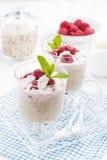 Dessert con la farina d'avena, la panna montata ed i lamponi, verticali Fotografia Stock
