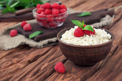 Dessert of cottage cheese and fresh raspberries. In a bowl on wooden table, copy space, at eye level Stock Images