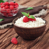 Dessert of cottage cheese and fresh raspberries. In a bowl on wooden table, copy space, at eye level Royalty Free Stock Photo