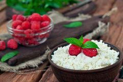 Dessert of cottage cheese and fresh raspberries. Cottage cheese and fresh raspberries in a bowl on a wooden table, copy space. rustic style. close-up Stock Image