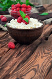 Dessert of cottage cheese and fresh raspberries. Cottage cheese and fresh raspberries in a bowl on a wooden table, copy space. rustic style. A eye level Royalty Free Stock Photography