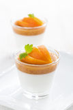 Dessert with cream and apricot jelly in glasses on white plate Royalty Free Stock Image