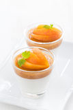 Dessert with cream and apricot jelly in glasses on white plate Stock Photos
