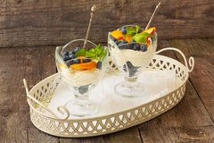 Dessert with cream cheese, blueberries and peaches Stock Images