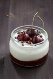 Dessert with cream and cherry jam on dark wooden background Royalty Free Stock Photography