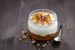 Dessert with cream, granola and peach jam on wooden table Royalty Free Stock Photos
