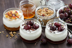 Dessert with cream and jam in glass jar on dark wooden table Royalty Free Stock Photos