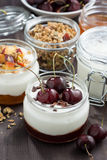 Dessert with cream and jam in glass jar on dark wooden table Stock Image