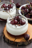 Dessert with cream and jam in glass jar, vertical Royalty Free Stock Images
