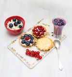 Dessert currant bilberry raspberry milk on a wooden board Royalty Free Stock Image