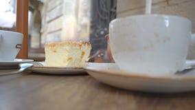 Dessert de fromage avec une tasse de café et d'une théière sur le café de rue banque de vidéos
