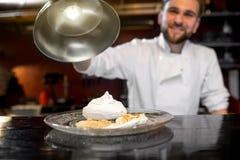 Dessert de portion de cuisinier de chef au client photos stock