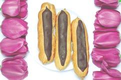 Dessert De zoete koekjes met chocolade zijn op een witte achtergrond naast kleurrijke tulpen stock foto