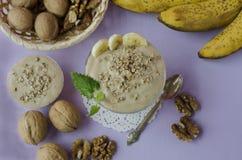 Dessert del gelato della banana con le noci su un fondo porpora fotografia stock