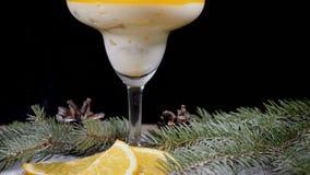 Dessert delizioso in ciotola di vetro sul bordo di legno decorato con i rami dell'abete e le fette di limone Isolato sul nero stock footage