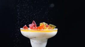 Dessert delizioso in ciotola di vetro sul bordo di legno decorato con i rami dell'abete e le fette di limone Isolato sul nero video d archivio