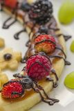 Dessert. From a slice of banana with berries and chocolate topping Royalty Free Stock Photography