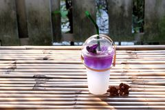 A glass of iced coconut milk mixed with butterfly pea soft drinks on bamboo table royalty free stock photos