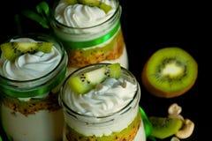 Dessert dolce naturale con il kiwi ed i dadi in barattoli di vetro sulla cucina fotografia stock