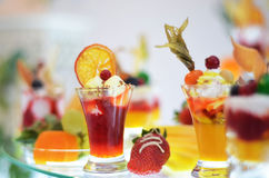 Dessert and drinks on buffet table. Sweet dessert with orange, strawberry, soft drinks at the event Stock Photo