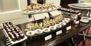 Dessert e forno di approvvigionamento sulla linea del buffet con la tonalità arancio all'angolo, fuoco selettivo della luce di Su Immagini Stock Libere da Diritti