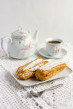 Dessert Eclair with whipped cream. And sugar icing on a white table Stock Photo