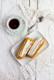 Dessert Eclair with whipped cream. And sugar icing on a white table Royalty Free Stock Images