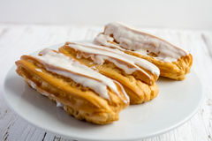 Dessert Eclair with whipped cream. And sugar icing on a white table Royalty Free Stock Photography