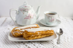 Dessert Eclair with whipped cream. And sugar icing on a white table Royalty Free Stock Photos