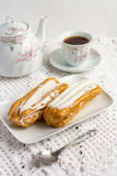 Dessert Eclair with whipped cream. And sugar icing on a white table Stock Image
