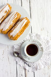 Dessert Eclair with whipped cream. And sugar icing on a white table Stock Photos
