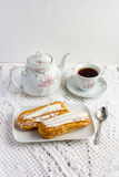 Dessert Eclair with whipped cream. And sugar icing on a white table Stock Images