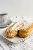 Dessert Eclair with whipped cream. And sugar icing on a white table Royalty Free Stock Image