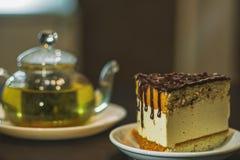 Dessert, een stuk van de melk van de vogel op de achtergrond van een glastheepot met groene thee stock foto's