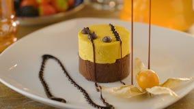 Dessert elegante sulla guarnizione di versamento del cioccolato del amd bianco del piatto stock footage