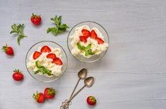 Dessert fait maison d'été avec le fromage de fraise et fondu coupé en tranches dans les bols en verre sur un fond gris avec l'esp Photographie stock